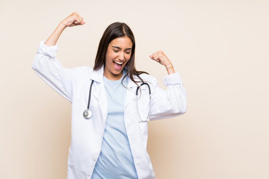 Young doctor woman over isolated background celebrating a victory