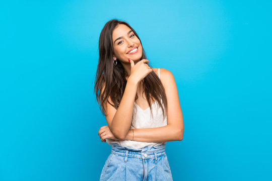 Young woman over isolated blue background smiling