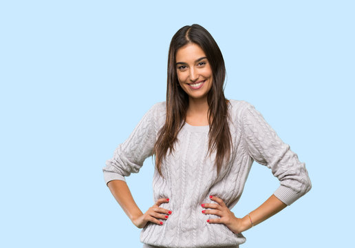 Young hispanic brunette woman posing with arms at hip and smiling over isolated background
