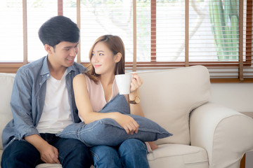 Beautiful young asian couple smiling and talking story married sitting on sofa at home together with woman holding a cup of coffee, man and woman relax and enjoy, lifestyle concept.