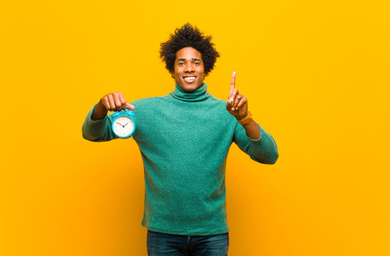 young african american man with an alarm clock against orange ba