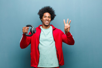 young black man sports man with a dumbbell against blue grunge w