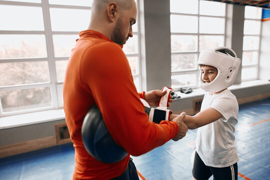 young man helping a boy to put on boxing gloves. close up side view photo. man preparing a kid for boxing