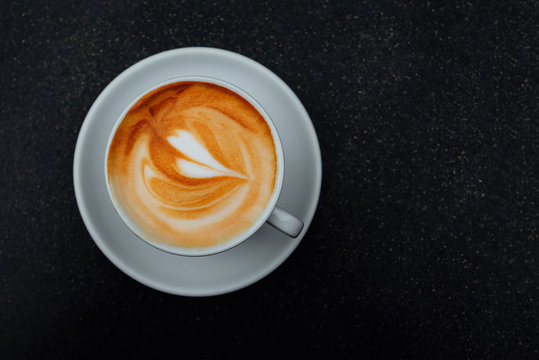 Fresh italian cappuccino coffee in a white cup on black background.