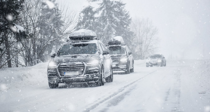 Winter road in beatiful forest. Snow calamity or blizzard. Fast cars on snowy roads in storm.
