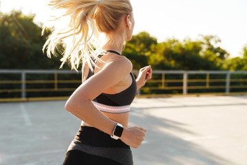 Image of attractive fitness woman wearing tracksuit running outdoors