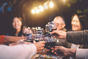 Happy family cheering with red wine at reunion dinner in garden - Senior having fun toasting wineglasses and dining together outdoor - People and food lifestyle concept