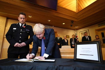 Britain's Prime Minister Boris Johnson signs a book of condolence during a visit to Thurrock Council Offices in Grays