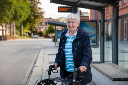 Very old senior woman waiting at the bus stop with walker