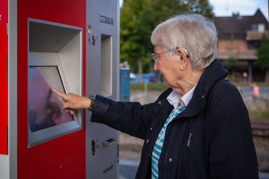 Closeup of very old senior woman buying a ticket on a ticket vending machine