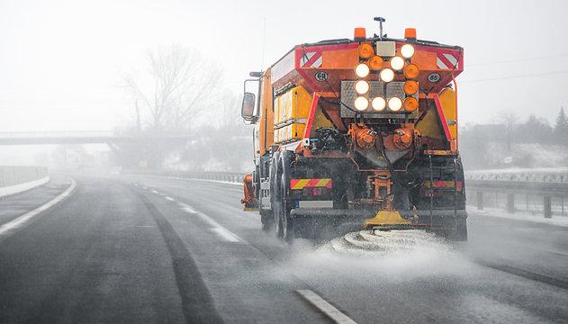 Snow plow salting street in winter time. Orange truck deicing. Maintenance winter vehicle back side.