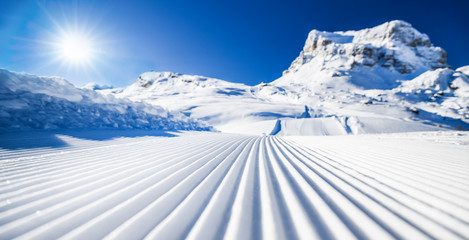 Poster Glisse hiver New groomed ski piste or slope. Lines in snow with sunny mountains background. Winter skis concept.