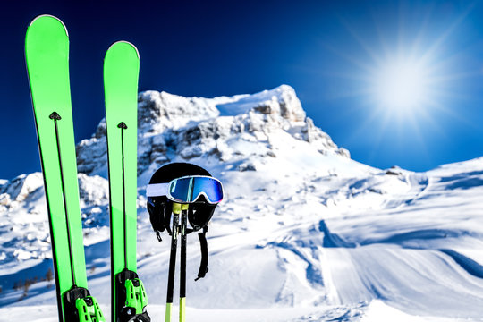 Skis in snow, mountains and ski concept equipments in sunny winter day. Fresh or new groomed slope at best piste resort.