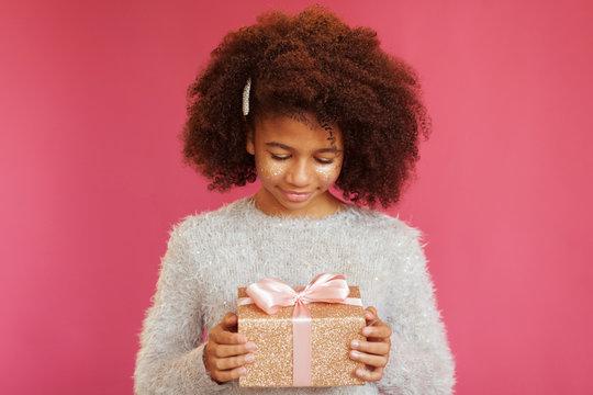Cute festive girl holding a shiny gift box