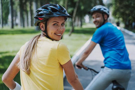 Joyful woman enjoying bicycle ride with her husband