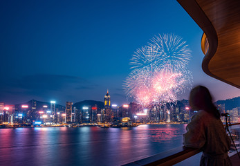 Fototapete - Woman watch firework show at Hong Kong Victoria Harbor  from Deluxe Hotel