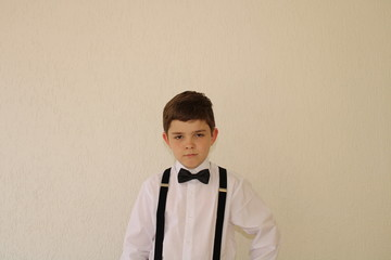 ten years old boy wearing social clothing with suspender and bow tie