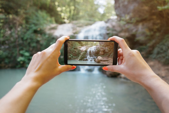 POV of hands taking a photo the waterfall with smartphone.
