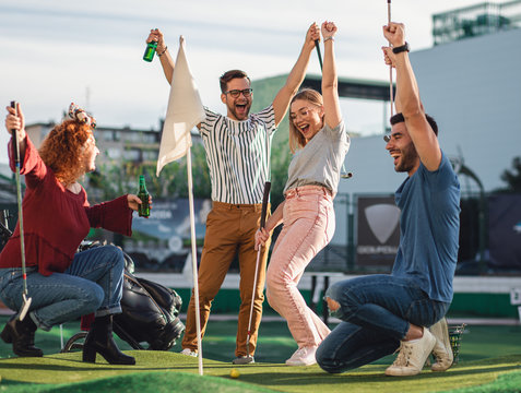 Group of smiling friends enjoying together playing mini golf in the city.