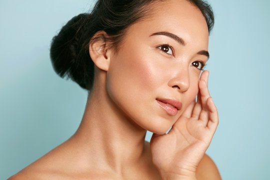 Skin care. Woman with beauty face and healthy facial skin portrait. Beautiful asian girl model with natural makeup touching glowing hydrated skin on blue background closeup. High quality image