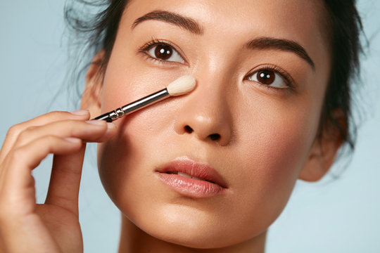 Beauty. Woman applying makeup on skin with cosmetic brush closeup. Portrait of asian female model with beautiful face doing facial make up at studio