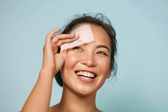 Face skin care. Smiling woman using facial oil blotting paper portrait. Closeup of beautiful happy asian girl model with natural makeup using oil absorbing sheets, beauty product at studio