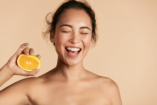 Beauty. Smiling woman with radiant face skin and orange portrait. Beautiful smiling asian girl model with natural makeup, healthy smile and glowing hydrated facial skin. Vitamin C cosmetics concept