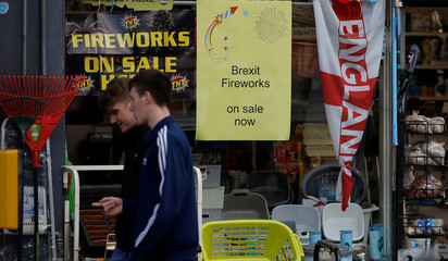 People walk past a sign advertising the sale of 'Brexit Fireworks' in the window of a hardware store near Manchester, Britain