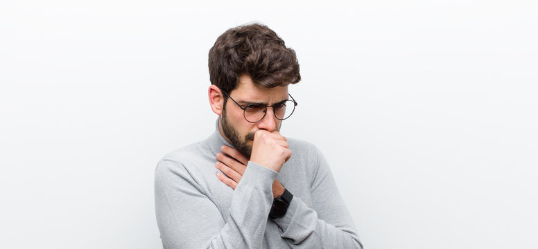young manager man feeling ill with a sore throat and flu symptoms, coughing with mouth covered against white wall