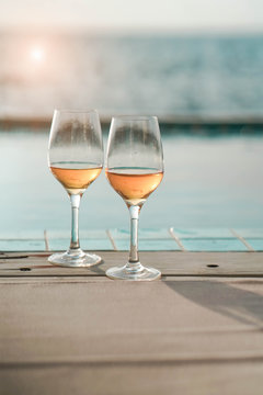 Two glasses of wine  on the edge of infinity swimming pool with panoramic views of the sea at sunset. Drink, celebrate, vacation and summer concept.
