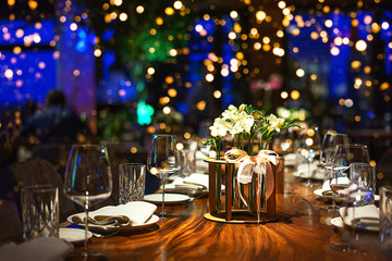 Blurred party background with served table with bouquet of flowers and people sitting at restaurant, bar or night club with colorful lights bokeh.