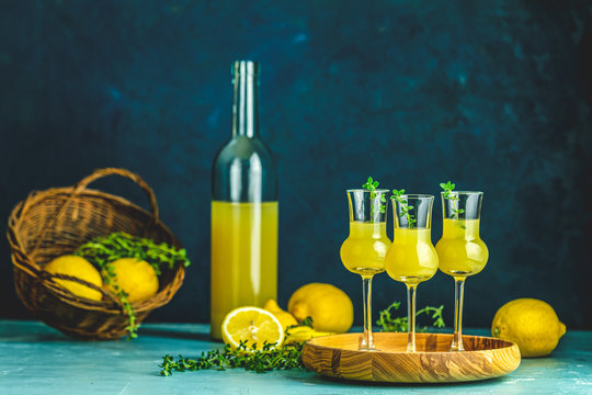 Limoncello with thyme in three grappas wineglass in wooden tray, fresh lemon in basket on dark blue background