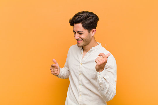 young handsome man smiling, feeling carefree, relaxed and happy, dancing and listening to music, having fun at a party against orange background