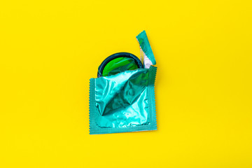 Condom half out of package on a yellow background. A condom use to reduce the probability of pregnancy or sexually transmitted disease (STD). Safe sex and reproductive health concept.
