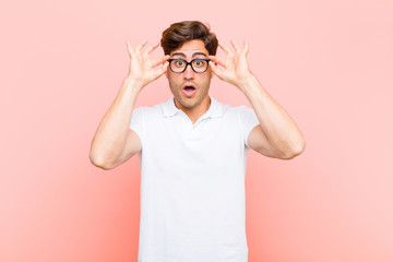 young handsome man feeling shocked, amazed and surprised, holding glasses with astonished, disbelieving look against pink background