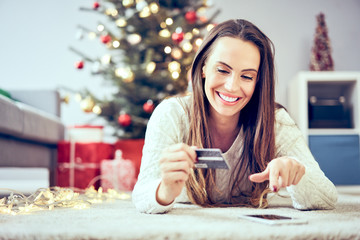 Young woman using credit card and phone to pay for Christmas shopping