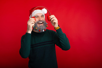 Cheerful man listening music over red background