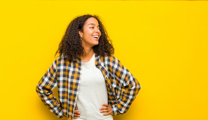 young pretty african american woman looking happy, cheerful and confident, smiling proudly and looking to side with both hands on hips against yellow wall