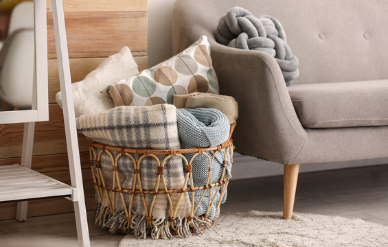 Basket with blankets and pillows near sofa indoors