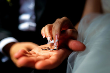 picture of man and woman with wedding ring. Bridal rings in man's hand. Hands closeup.