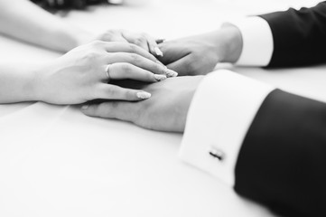 picture of man and woman holding hands. Wedding ceremony. Groom and bride. Wife and husband. Black and white photo. Closeup.