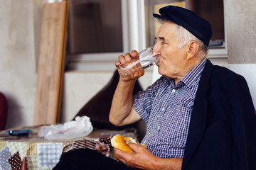 Senior old man pensioner drinking water while eating fast food burger sitting by the plastic table at the store by the window outdoor
