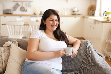 Portrait of cheerful charismatic young overweight female with big breast and long black hair posing in stylish kitchen interior, having coffee on comfortable couch and laughing at funny joke