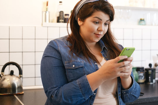 Cute chubby female with loose dark hair standing in kitchen interior with smart phone, looking at screen with astonished facial expression, receiving good news via text message from her friend