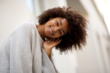 Close up happy young african american woman with curly hair smiling outside Wall mural