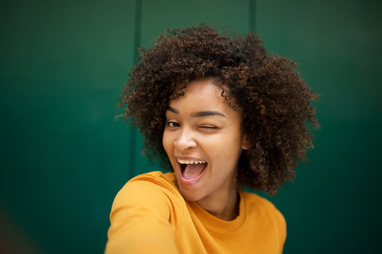 happy african american young woman taking selfie with winking eye