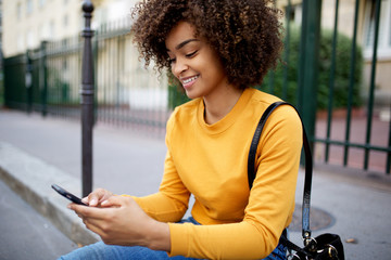 smiling african american woman looking at cellphone in city Wall mural