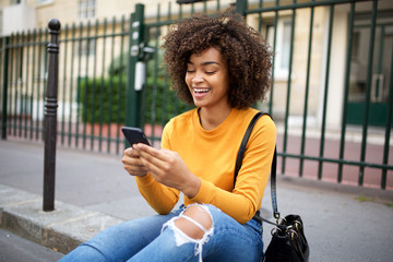 smiling african american young woman looking at cellphone in city