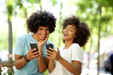 young afro man with mobile phone looking at happy african american woman cellphone