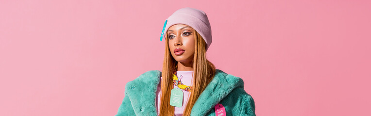panoramic shot of thoughtful, stylish african american woman with tags on clothing isolated on pink, fashion doll concept